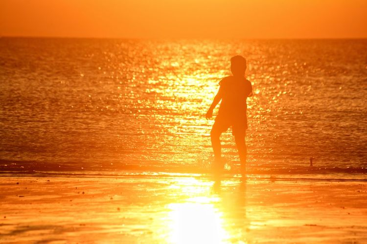 Sunset Sea Orange Color Back Lit Silhouette One Person Sunlight Beach Reflection Standing Vacations Nature Water Beauty In Nature Outdoors Sun Yellow Summer People