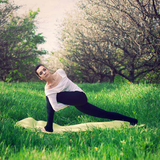 Young Woman Doing Yoga On Field