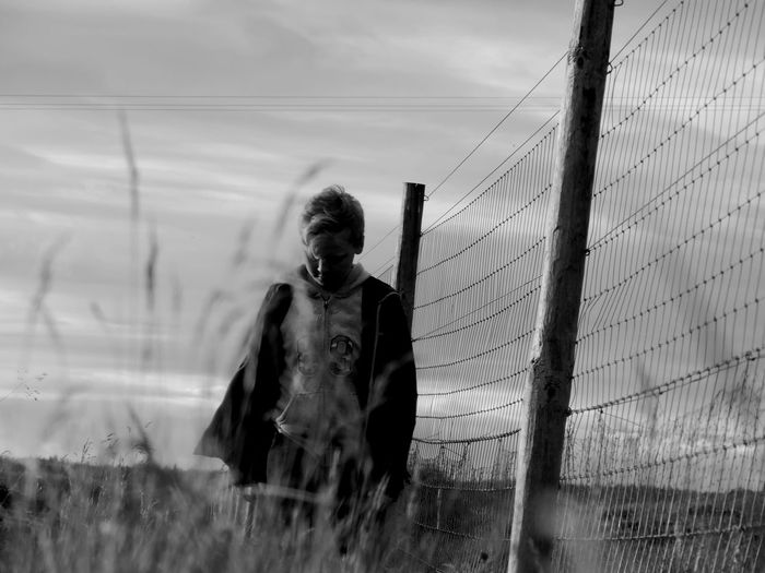 Boy Standing By Fence Against Sky