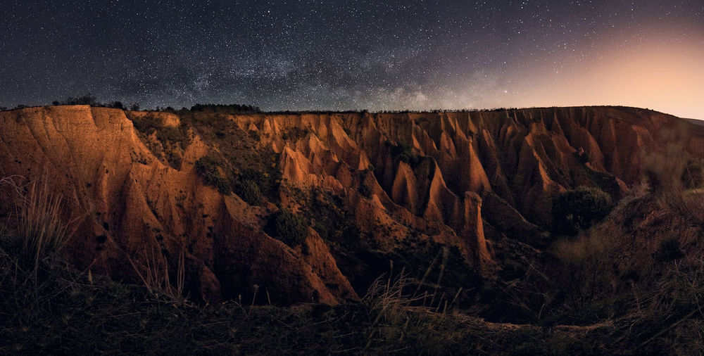 Scenic view of rock formations against sky at night. milkyway panoramic