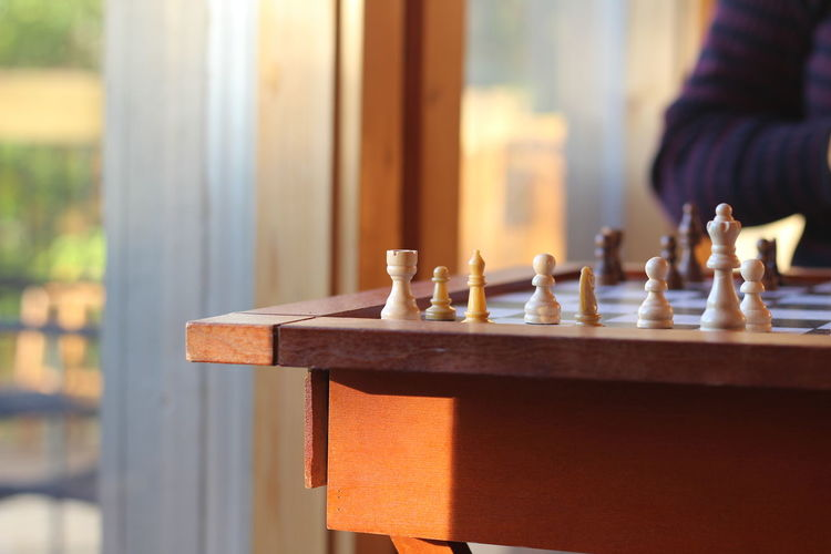 Cropped image of person by chess board