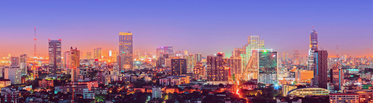 Panoramic view of illuminated city buildings against sky
