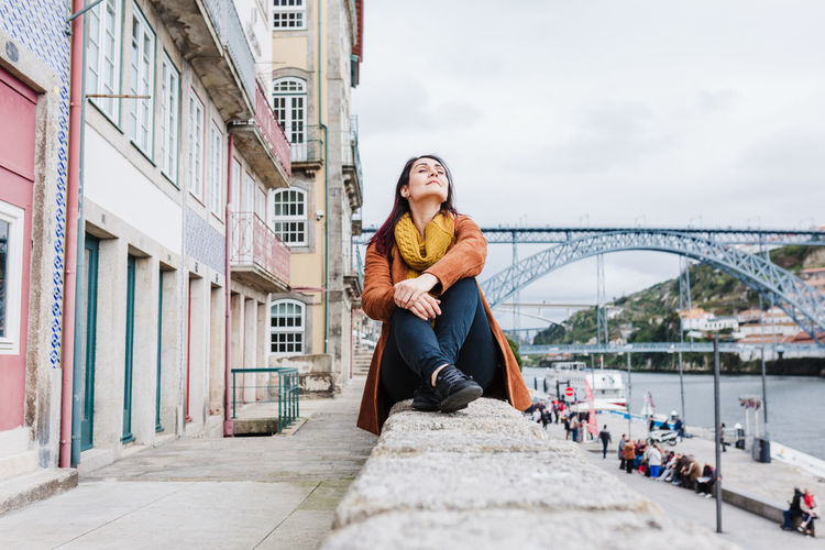 Young woman sitting on bridge over river in city