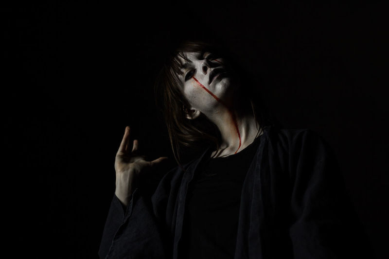 Portrait of young woman with halloween make-up against black background