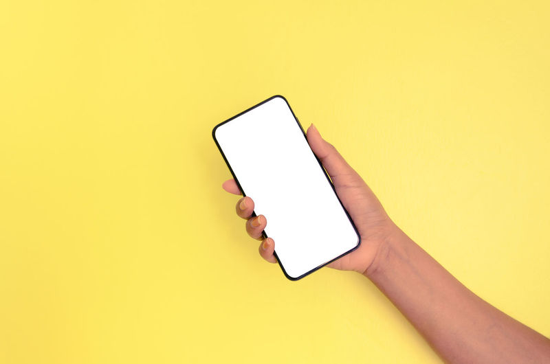 Low angle view of person using smart phone against yellow background