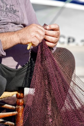 Midsection of man holding fishing net