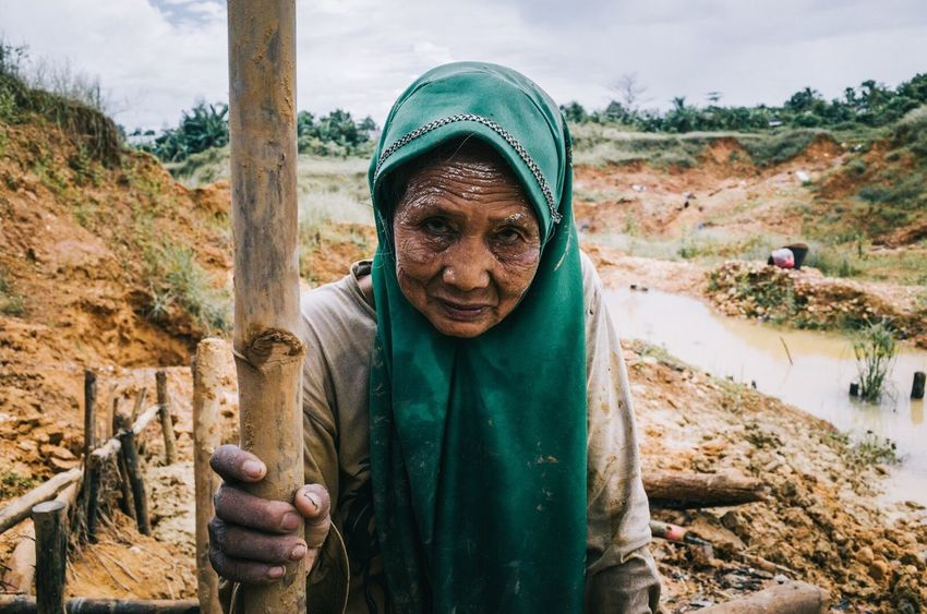 Her gaze was very friendly but keep the spirit of hard work to dig the diamond mine pits with her relatives. • Women Around The World Looking At Camera Portrait Real People Front View Outdoors One Person Day Nature Smiling Happiness Tree Human Hand Sky Men Old Woman Human Body Part Mine Miner Work Resist The Portraitist - 2017 EyeEm Awards