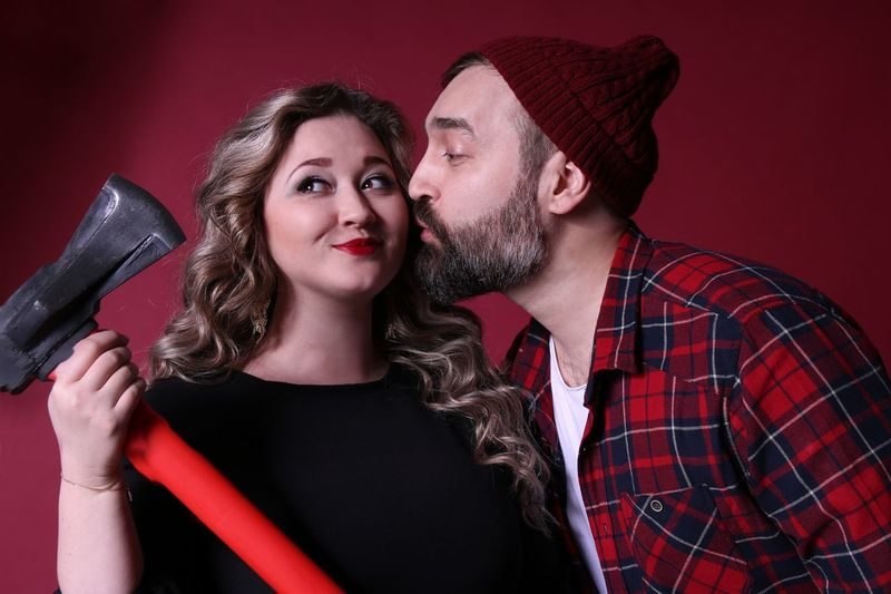 Man Kissing Girlfriend Holding Axe By Red Wall