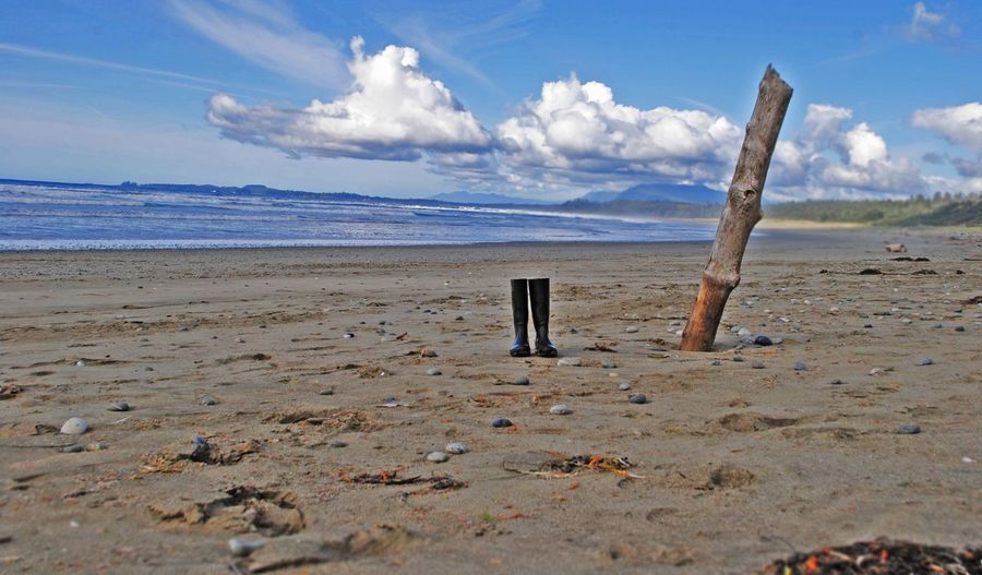 Rubber boots on beach against sky
