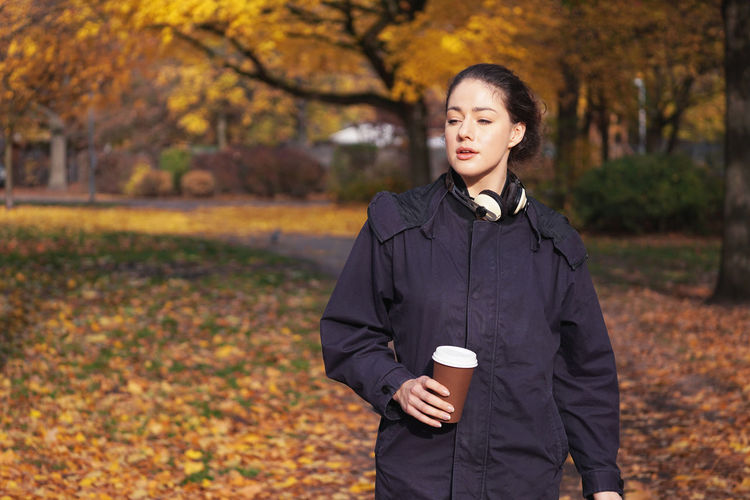 One Person Autumn Young Adult Front View Real People Tree Leisure Activity Day Nature Lifestyles Outdoors Beautiful Woman Girl People Young Woman Fall Walking Candid Waist Up Cup Coffee Cup Contemplation Copy Space Park Walk Hipster Coffee To Go Headphones Sunny