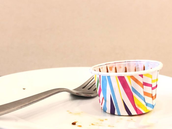 Empty dessert paper cup with stainless fork on a part of white plate over the off-yellow background. EyeEm Selects Kitchen Utensil Still Life Copy Space Table Fork Eating Utensil No People Indoors  Multi Colored Studio Shot Close-up Plate Food Striped Food And Drink Paper
