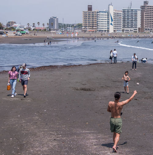 People on beach in city
