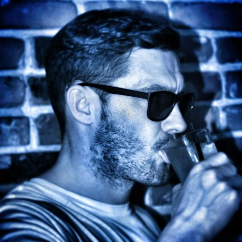 Close-Up Of Man Wearing Sunglasses While Having Drink Against Brick Wall