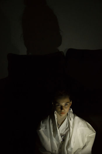 Portrait of a boy looking away against black background