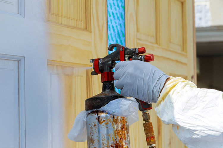 Hand with spray gun painting wooden door use for home decorated Craftsman Gun Paint Repairing Spraying Work Air Tools Airbrush Door Equipment Hand House Painter Land Vehicle Paint Spray Gun Painter Painting People Pneumatic Pulverizer Repair Spray Paint Spray Painter Timber Wood - Material Woodworking
