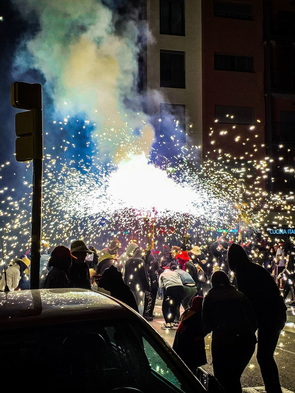 group of people, night, crowd, large group of people, real people, illuminated, smoke - physical structure, event, celebration, arts culture and entertainment, built structure, architecture, city, enjoyment, transportation, men, building exterior, outdoors, motion, light, firework display, firework