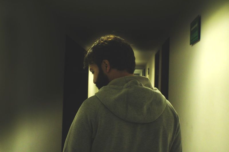 Rear view of a man standing in corridor