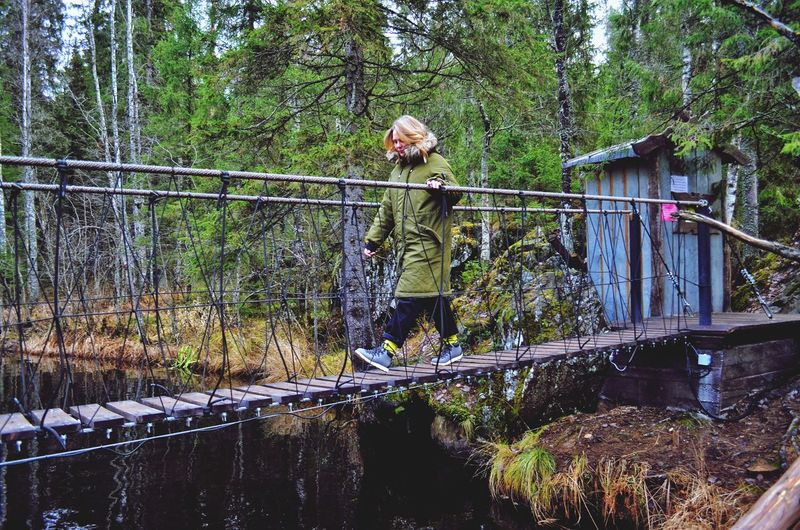 Woman walking on footbridge in forest