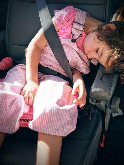 High angle view of girl sleeping on car seat