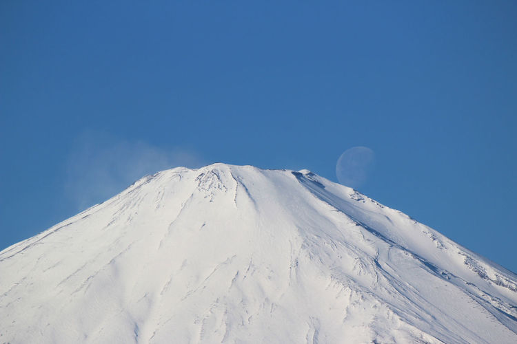 Low angle view of snow covered mt fuji against sky