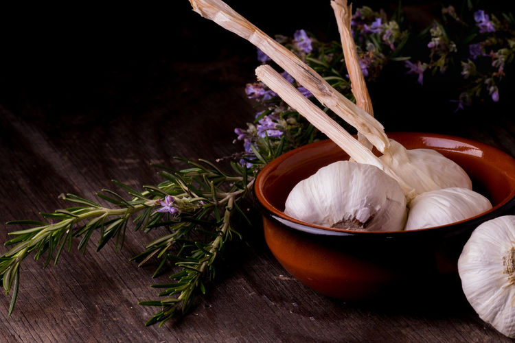 Garlic and rosemary on wooden table Rosemary Rustic Bowl Close-up Day Flower Food Food And Drink Freshness Garlic Garlic Bulb Healthy Eating Indoors  Nature No People Raw Food Rosemary Herb Rustic Style Table Wood - Material