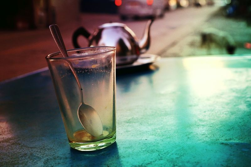 Close-up of spoon in glass on table against street