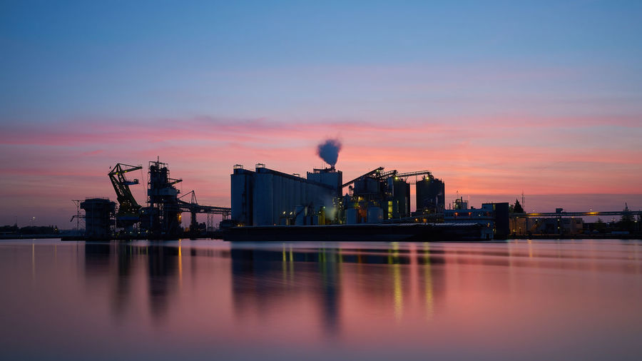 Industrial Buildings By River Against Sky During Sunset
