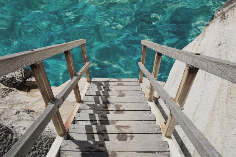 Wooden stairs leading to calm water