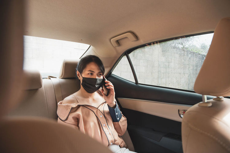Businesswoman wearing mask talking on phone sitting in car