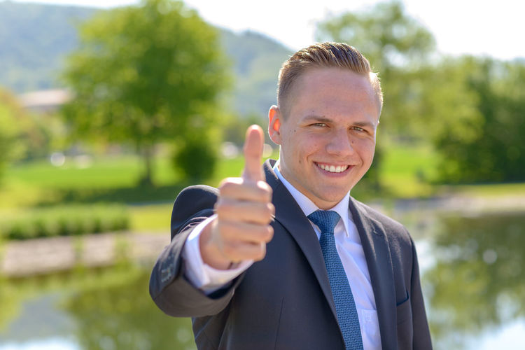 Close-up portrait of businessman gesturing thumbs up sign in sunny day