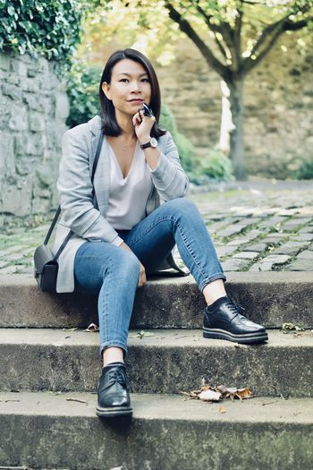 Portrait of young woman sitting on staircase outdoors
