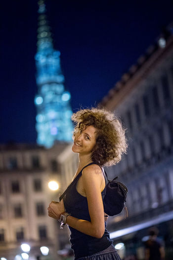 Adult Architecture Beautiful Woman Building Building Exterior Built Structure City Curly Hair Focus On Foreground Hair Hairstyle Illuminated Lifestyles Night One Person Standing Waist Up Women Young Adult Young Women
