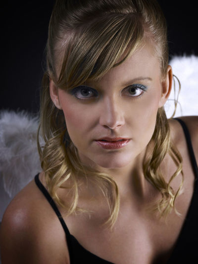 caucasian angel on the black background Beautiful People Slim Standing Angel Angel Wings Attractive Beautiful Woman Beauty Black Background Blond Hair Blonde Hair Caucasian Close-up Front View Indoors  Long Hair Looking At Camera One Person Portrait Pretty Real People Wing Costume Women Young Adult Young Women