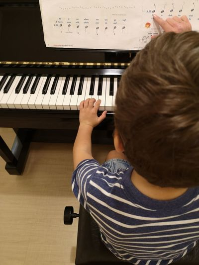Rear view of boy playing piano