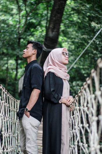 Couple standing back to back on footbridge in forest