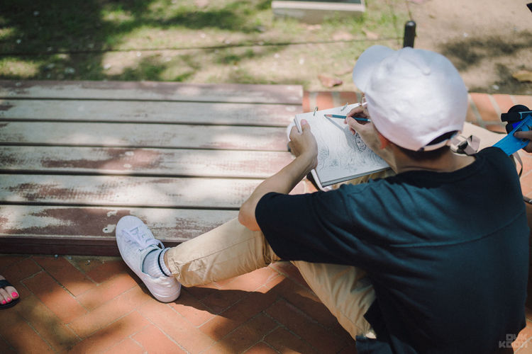 Rear View Of Boy Drawing On Book While Sitting On Bench Outdoors