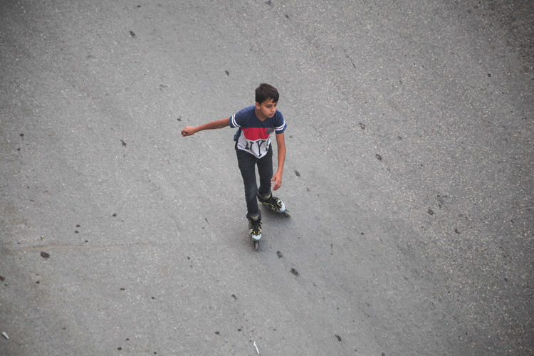 High angle view of boy standing on skateboard