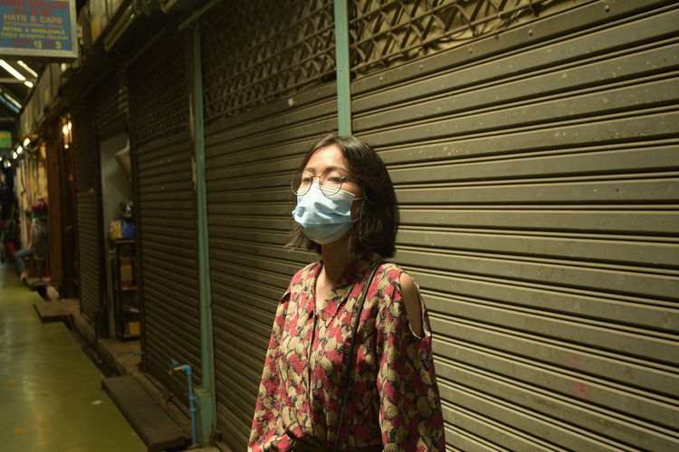 Portrait of woman wearing mask standing against closed shutter