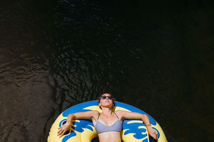 High angle view of woman relaxing in inflatable ring over lake
