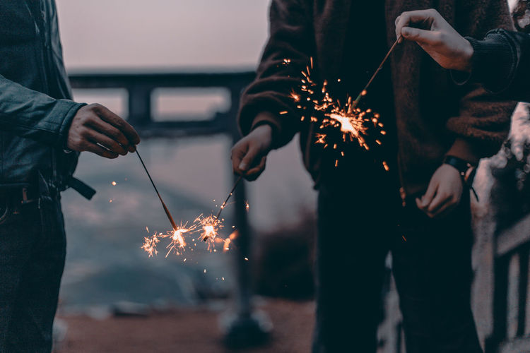 Midsection Of People Holding Sparklers At Night