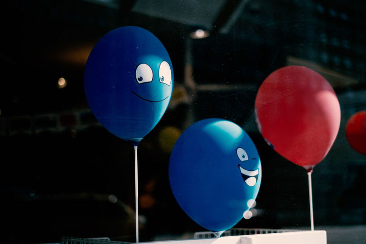Close-up of multi colored balloons with smiley face