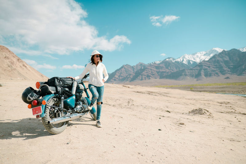 Mid Adult Woman With Motorcycle Standing On Desert Against Blue Sky During Sunny Day