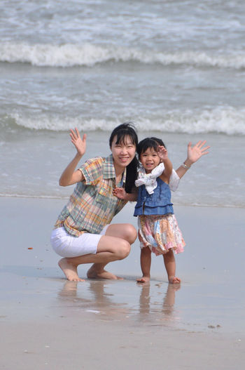 Full length of mother and daughter on beach