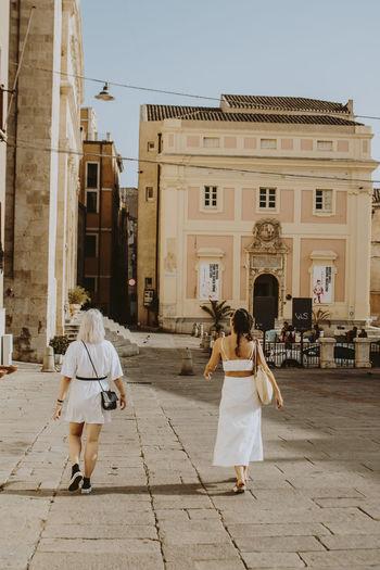Rear view of people walking on street against buildings