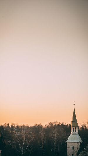 Church by building against orange sky