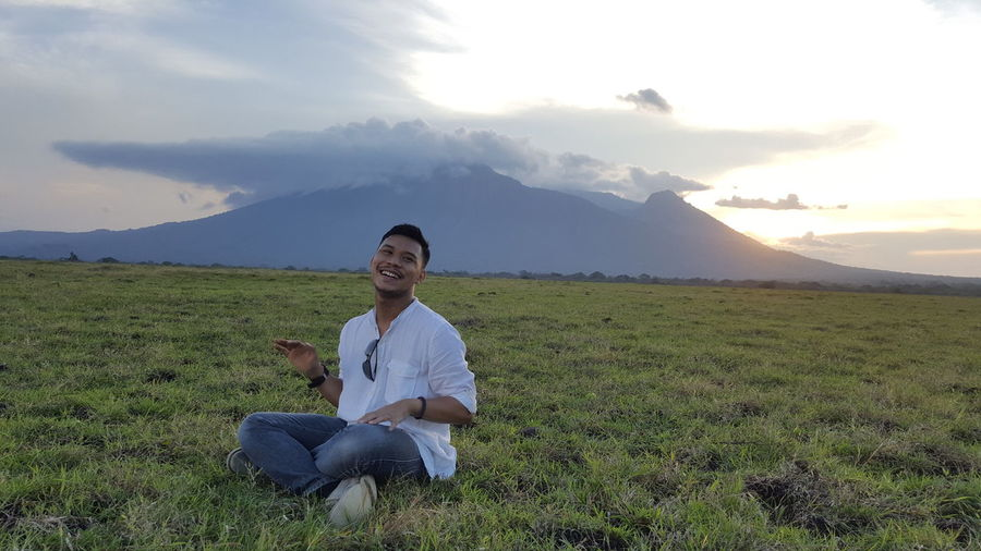 Full length of smiling man sitting on field against sky