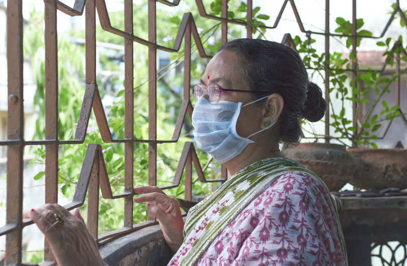 An indian woman looking outside from her house verandah. at kolkata during covid lockdown period.