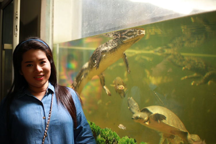 Portrait of woman standing by crocodile in fish tank