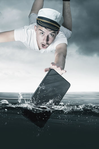 Digital composite image of man and sea against sky