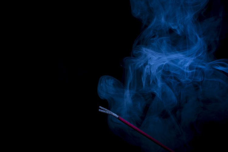 Close-Up Of Incense Burning Against Black Background